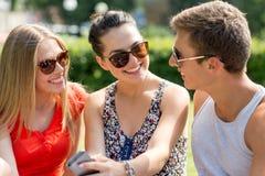 Amigos sonrientes con el smartphone que se sienta en parque Imágenes de archivo libres de regalías