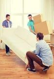 Amigos sonrientes con el sofá y las cajas en el nuevo hogar Fotografía de archivo libre de regalías
