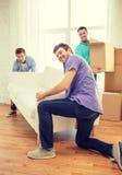 Amigos sonrientes con el sofá y las cajas en el nuevo hogar Fotos de archivo libres de regalías