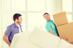 Amigos sonrientes con el sofá y las cajas en el nuevo hogar Foto de archivo