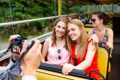Amigos sonrientes con la cámara que viaja en bus turístico Imagen de archivo libre de regalías