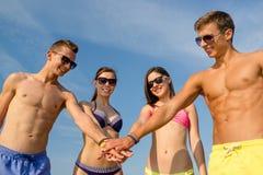 Amigos sonrientes con la mano en el top al aire libre Imágenes de archivo libres de regalías