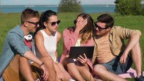 Amigos sonrientes con la PC de la tableta que se sienta en hierba almacen de video