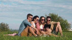 Amigos sonrientes con la PC de la tableta que se sienta en hierba metrajes