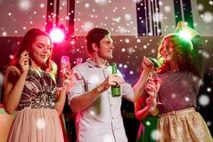 Amigos sonrientes con las copas de vino y la cerveza en club Imágenes de archivo libres de regalías