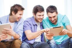 Amigos sonrientes con los ordenadores de la PC de la tableta en casa Fotografía de archivo