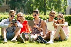 Amigos sonrientes con los ordenadores de la PC de la tableta en parque fotos de archivo libres de regalías