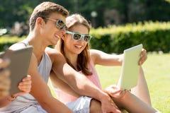 Amigos sonrientes con los ordenadores de la PC de la tableta en parque Imagen de archivo libre de regalías