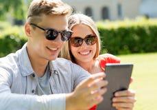 Amigos sonrientes con los ordenadores de la PC de la tableta en parque Fotografía de archivo libre de regalías
