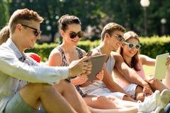 Amigos sonrientes con los ordenadores de la PC de la tableta en parque Imagenes de archivo