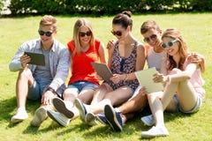 Amigos sonrientes con los ordenadores de la PC de la tableta en parque Foto de archivo libre de regalías