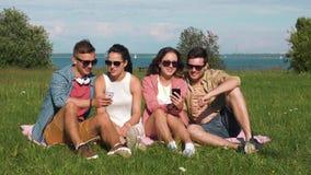 Amigos sonrientes con los smartphones que se sientan en hierba almacen de metraje de vídeo