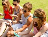 Amigos sonrientes con los smartphones que se sientan en hierba Foto de archivo libre de regalías