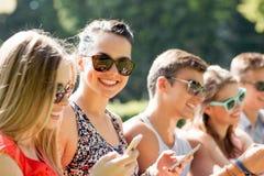 Amigos sonrientes con los smartphones que se sientan en parque Imagen de archivo