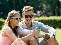 Amigos sonrientes con los smartphones que se sientan en parque Fotos de archivo libres de regalías