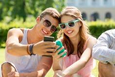 Amigos sonrientes con los smartphones que se sientan en parque Foto de archivo libre de regalías