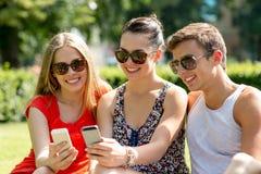 Amigos sonrientes con los smartphones que se sientan en parque Fotografía de archivo libre de regalías