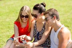 Amigos sonrientes con los smartphones que se sientan en parque Foto de archivo