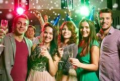 Amigos sonrientes con los vidrios de champán en club Fotos de archivo