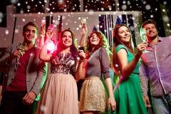 Amigos sonrientes con los vidrios de champán en club Fotografía de archivo libre de regalías