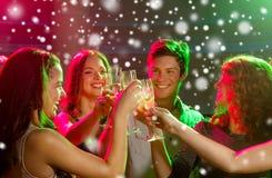 Amigos sonrientes con los vidrios de champán en club Fotografía de archivo