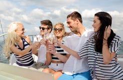 Amigos sonrientes con los vidrios de champán en el yate Fotografía de archivo libre de regalías