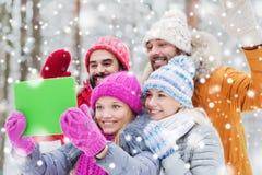 Amigos sonrientes con PC de la tableta en bosque del invierno Foto de archivo libre de regalías