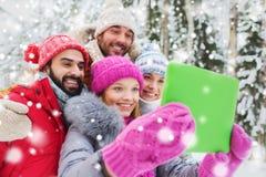 Amigos sonrientes con PC de la tableta en bosque del invierno Imagen de archivo libre de regalías