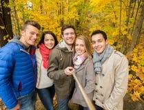Amigos sonrientes con smartphone en parque de la ciudad Imagen de archivo