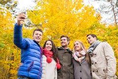 Amigos sonrientes con smartphone en parque de la ciudad Imágenes de archivo libres de regalías