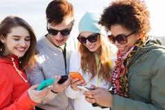 Amigos sonrientes con smartphones Imagen de archivo libre de regalías