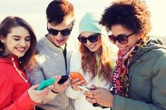 Amigos sonrientes con smartphones Fotos de archivo libres de regalías