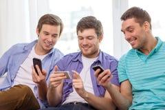 Amigos sonrientes con smartphones en casa Fotografía de archivo libre de regalías