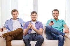 Amigos sonrientes con smartphones en casa Imagen de archivo