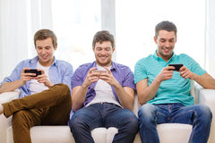 Amigos sonrientes con smartphones en casa Imagenes de archivo