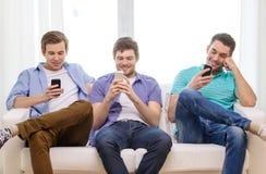 Amigos sonrientes con smartphones en casa Fotografía de archivo
