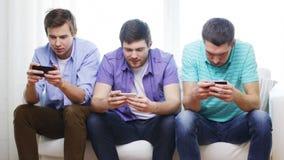 Amigos sonrientes con smartphones en casa metrajes