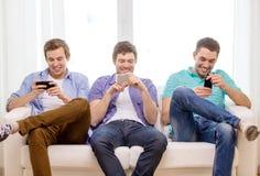 Amigos sonrientes con smartphones en casa Imagen de archivo libre de regalías
