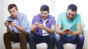 Amigos sonrientes con smartphones en casa almacen de metraje de vídeo
