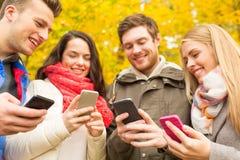 Amigos sonrientes con smartphones en parque del otoño Fotos de archivo