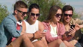 Amigos sonrientes con smartphones en parque del verano almacen de metraje de vídeo