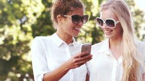 Amigos sonrientes con usar smartphone almacen de metraje de vídeo