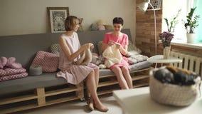 Amigos sonrientes de la mujer que hablan en el sofá y agujas que hacen punto en el taller casero almacen de metraje de vídeo