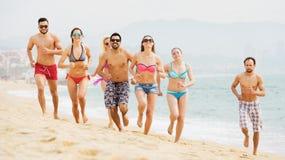 Amigos sonrientes de los adultos que corren en la playa Fotos de archivo libres de regalías