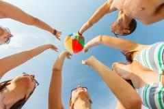 Amigos sonrientes en círculo en la playa del verano Fotografía de archivo