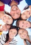 Amigos sonrientes en círculo en la playa del verano Imágenes de archivo libres de regalías