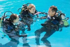 Amigos sonrientes en el entrenamiento del equipo de submarinismo en piscina Imagen de archivo
