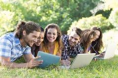 Amigos sonrientes en el parque usando la PC y el ordenador portátil de la tableta Fotos de archivo