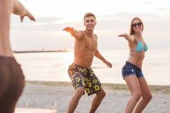 Amigos sonrientes en gafas de sol con resacas en la playa Imágenes de archivo libres de regalías