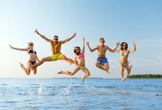 Amigos sonrientes en gafas de sol en la playa del verano Imágenes de archivo libres de regalías